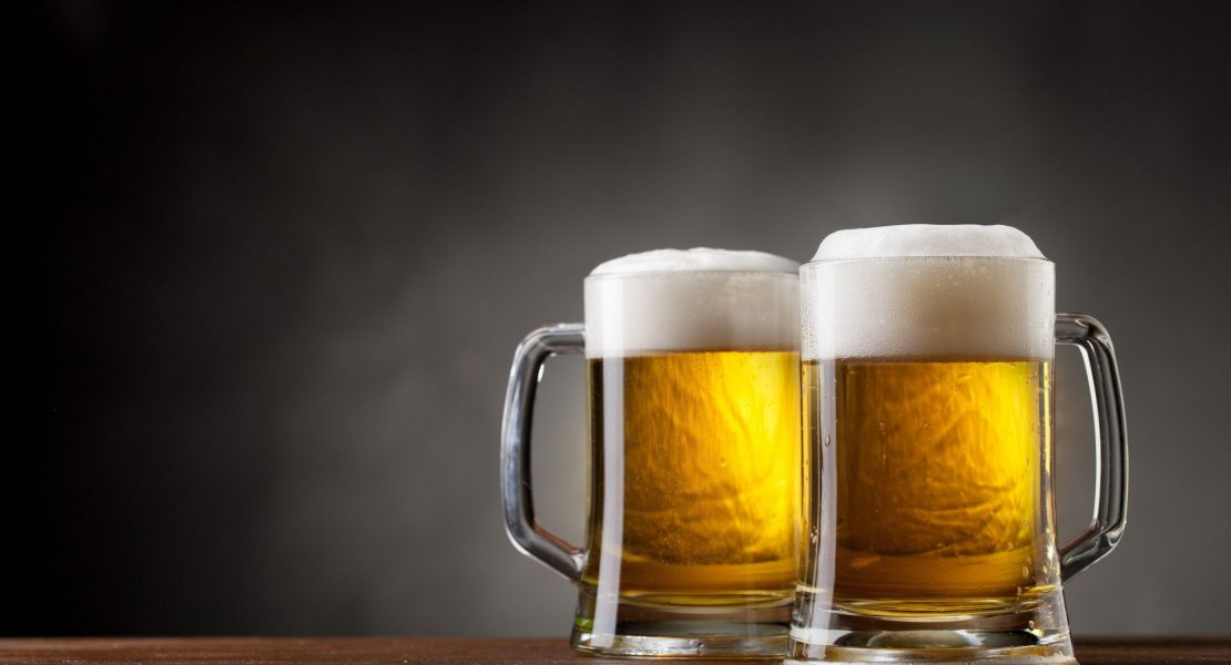 Two beer glasses with a dark background